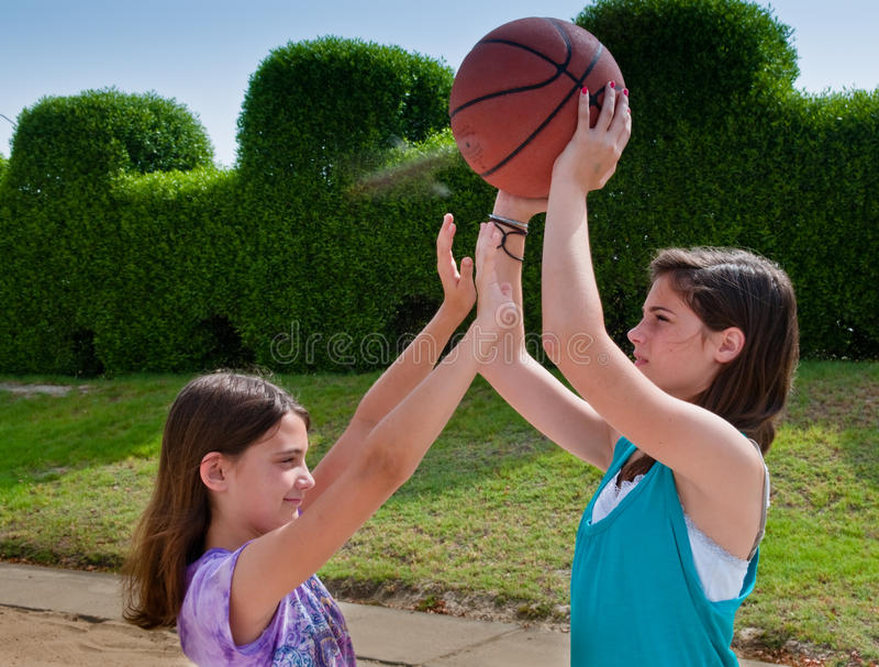 One on One Ball. Two sisters playing basketball in an outdoor park stock photo