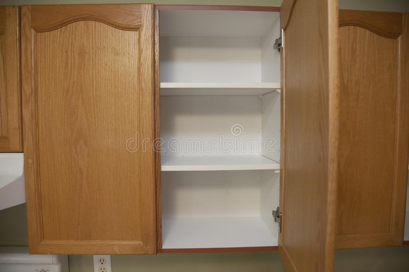One open cupboard. Kitchen cupboard with wooden doors and open to see empty shelves stock image