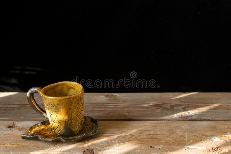 One orange hand made cup for coffee with saucer on the old wooden table with sunshine and black background. One orange hand made cup for coffee with saucer on stock photos