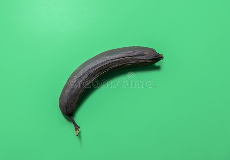One overripe banana isolated on green background stock photo