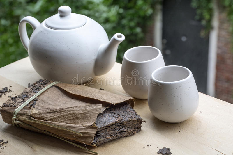 One pack of black tea with white teakettle and two cups. With green leaves as background stock photography
