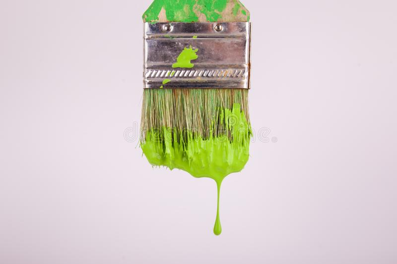 One paint drop dripping from paintbrush lime green paint. One lime green paint drop dripping from a paintbrush vertically white background stock photos