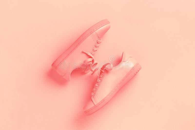 One pair of coral shoes on coral background. Pair of coral shoes on coral background. Trendy Living Coral color of the year 2019. Monochrome image royalty free stock image