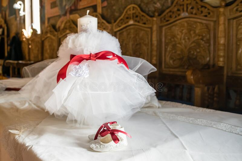 One pair of White bootees and big white candle for baby baptism party shower with red ribbon. In Romanian church, waiting the priest. White lace and red stock images
