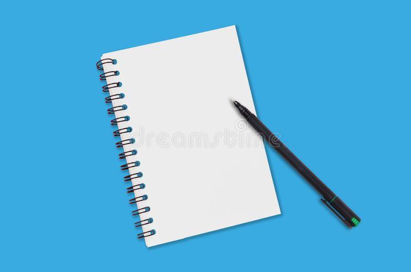 One paper notepad with spiral binder and blank sheets near black plastic pen lies of blue office table. Top view. Copy space for y royalty free stock images