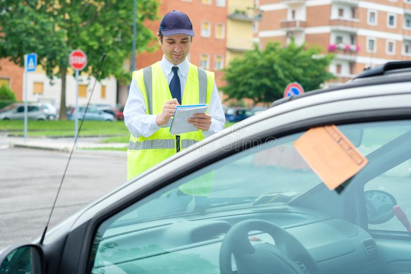 One parking warden writing a ticket for a parking violation. Parking officer writing parking charge notice time limit royalty free stock photo
