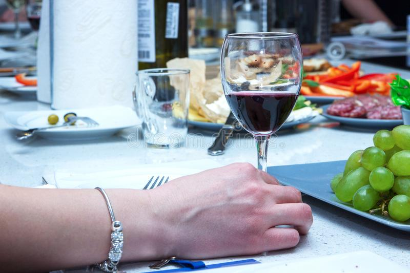 One of partying girls clinking flutes with sparkling wine. Girls hand with bracelet hold a glass of red wine. One of partying girls clinking flutes with stock images