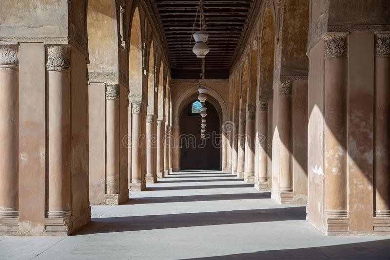 One of the passages surrounding the courtyard of the Mosque of Ahmad Ibn Tulun framed by huge decorated arches, Cairo, Egypt stock photography