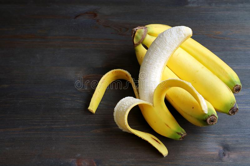 One peeled banana on a bunch of bananas isolated on dark brown wooden table royalty free stock photography