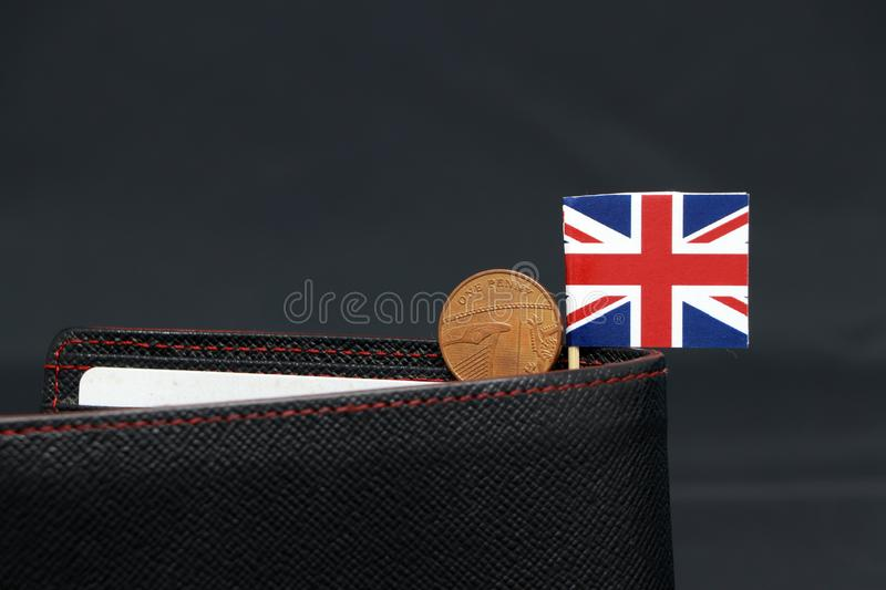 One Penny British decimal coin money and mini Union Jack flag stick on the black wallet with dark background stock image