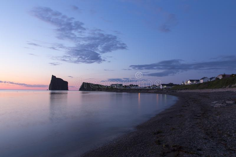 One of the Percé village beaches and cliffs and its famous rock seen during a beautiful summer blue hour sunrise. Quebec, Canada stock images
