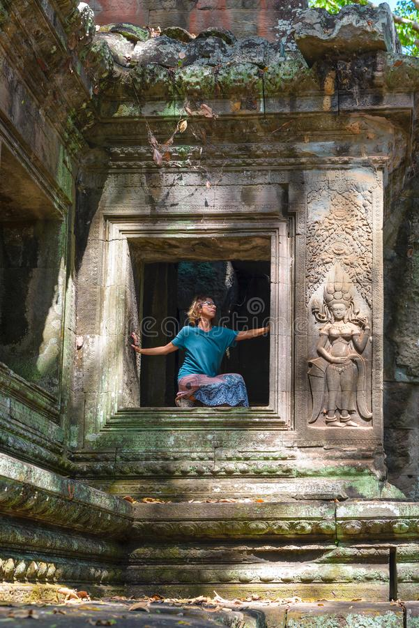 One person in Angkor Wat ruins, travel destination Cambodia. Woman in yoga position, stretching leg and raised arm, profile view, royalty free stock images