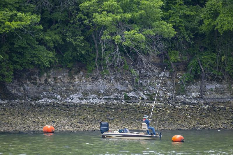 One person fishing in an outboard motor fishing boat near bouys under a high embankment with lots of very green trees up high. One person fishing in an outboard stock images
