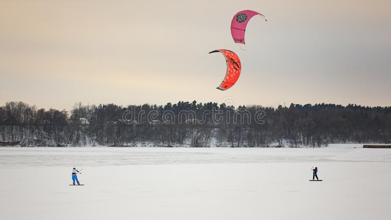 One person kiting with colorful kites in winter on snow stock images
