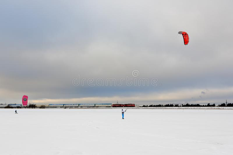 One person kiting with colorful kites in winter on snow royalty free stock photo