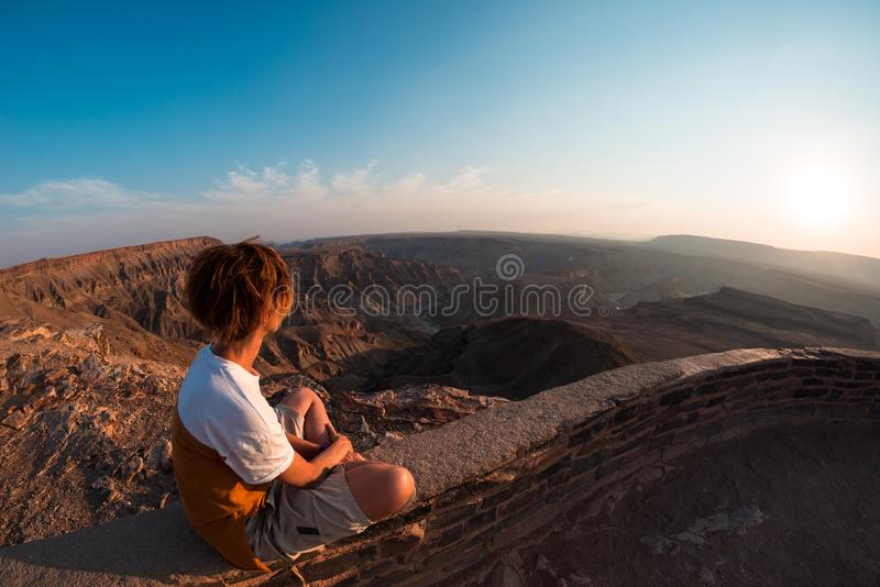 One person looking at the Fish River Canyon, scenic travel destination in Southern Namibia. Expansive view at sunset. Wanderlust t stock images
