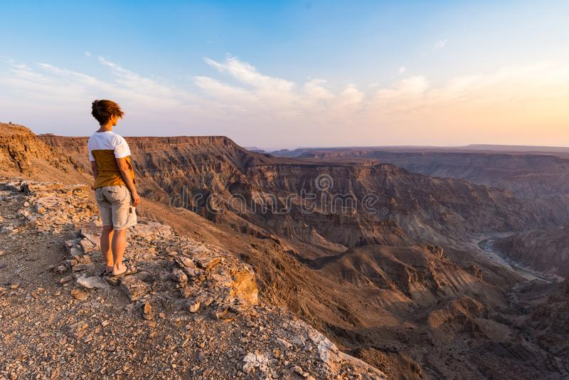 One person looking at the Fish River Canyon, scenic travel destination in Southern Namibia. Expansive view at sunset. Wanderlust t royalty free stock images