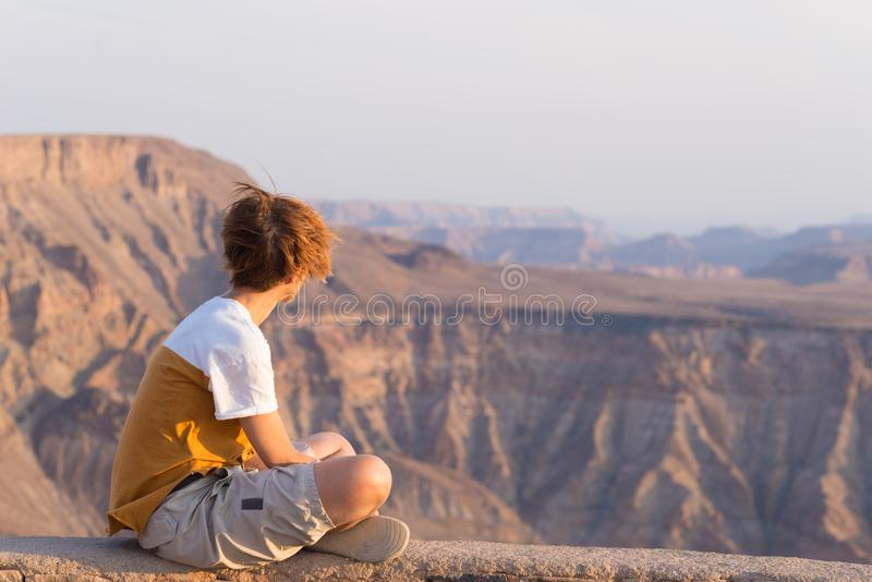 One person looking at the Fish River Canyon, scenic travel destination in Southern Namibia. Expansive view at sunset. Wanderlust t royalty free stock image