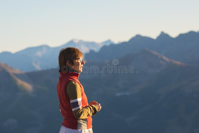 One person looking at the majestic view of glowing mountain peaks at sunset high up on the Alps. Rear view, toned and filtered ima royalty free stock images