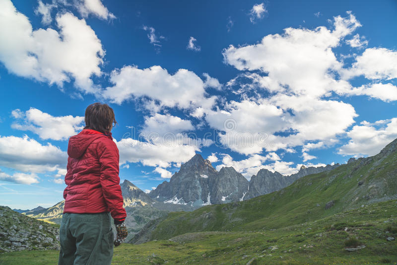 One person looking at the majestic view of glowing mountain peaks at sunset high up on the Alps. Rear view, toned and filtered ima royalty free stock image