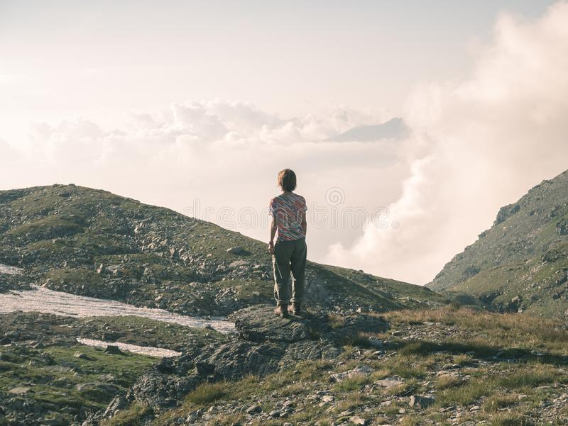One person looking at view high up on the Alps. Expasive landscape, idyllic view at sunset. Rear view, toned image. royalty free stock photo