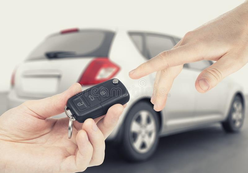 One person passing car-keys to another person with car on background. One person passing car keys to another person with car on background stock image