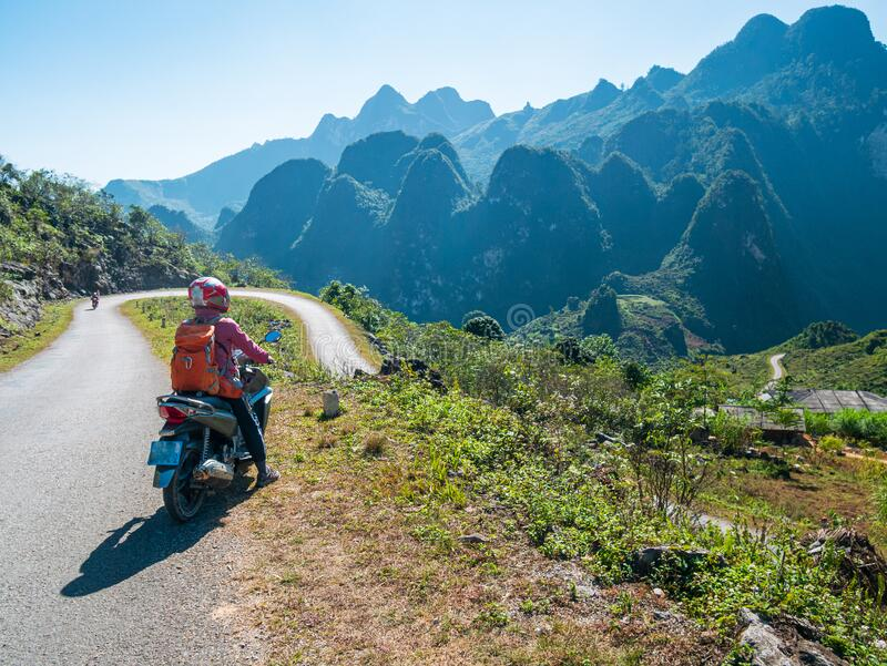 One person riding bike on Ha Giang motorbike loop, famous travel destination bikers easy riders. Ha Giang karst geopark mountain stock photo