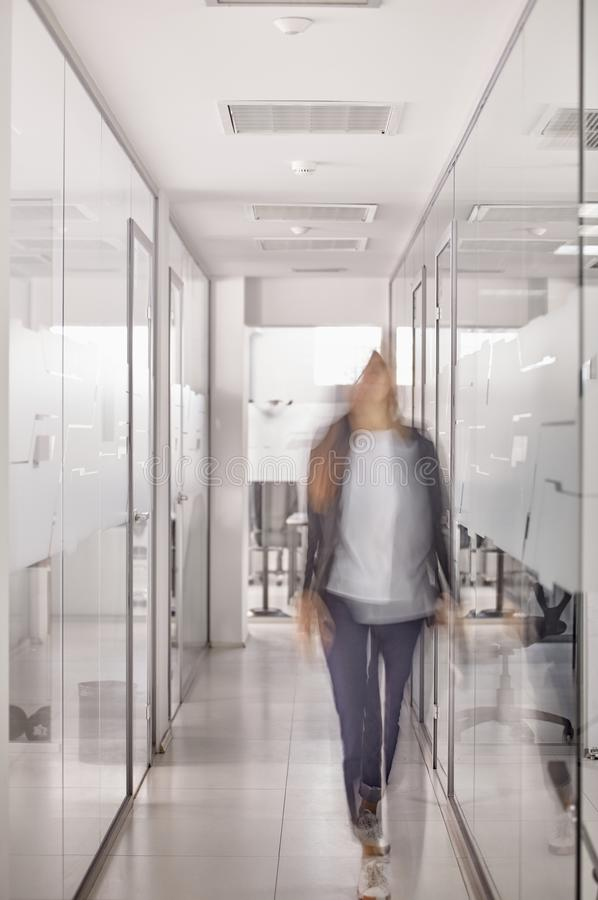 One person walking in modern business office hallway, motion blur, unrecognizable person stock photos