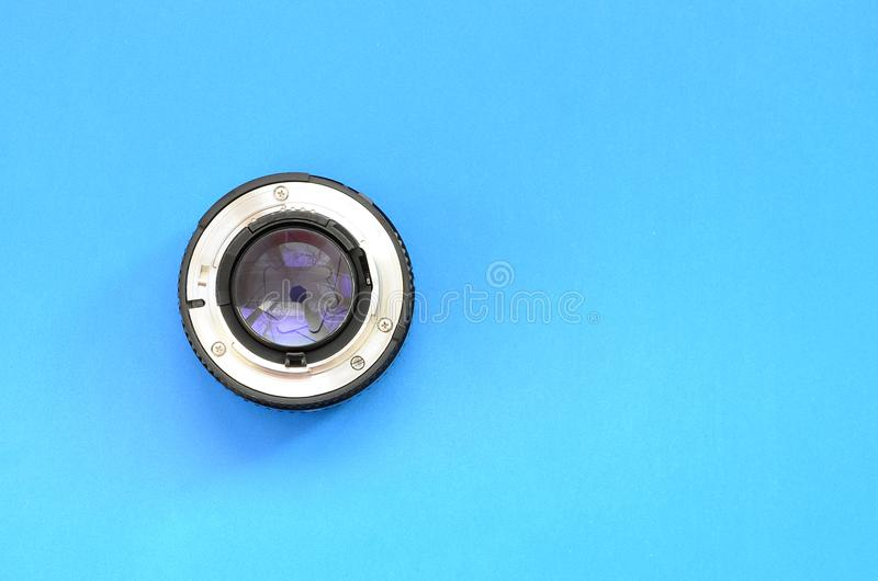 One photographic lense lie on a bright blue background. Space fo. R text royalty free stock photos