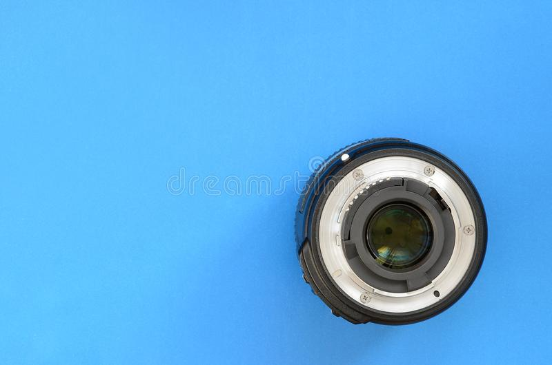 One photographic lense lie on a bright blue background. Space fo royalty free stock photos