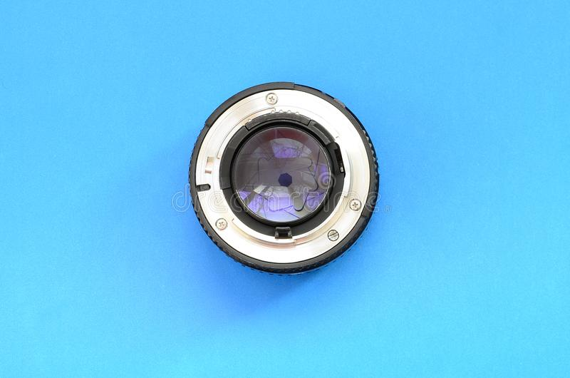 One photographic lense lie on a bright blue background. Space fo stock photography