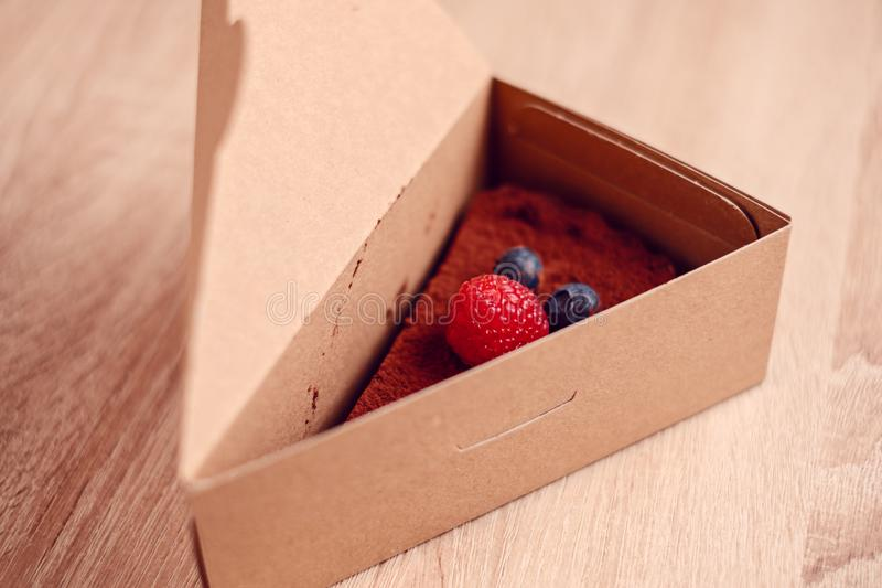 One piece of chocolate tart with raspberry and blueberries on top in cardboard box. Ready for take away stock image