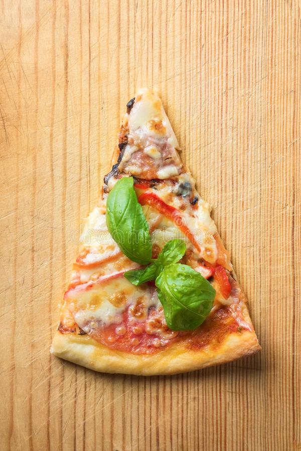 One piece of Italian pizza with tomatoes mushrooms bacon and cheese and basil leaves on wooden background cutting board stock image