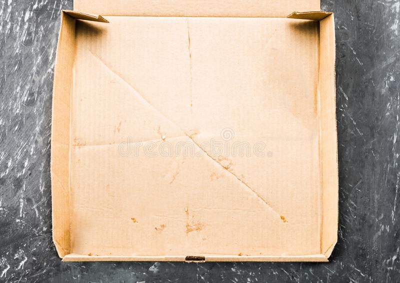 One piece of pizza in cardboard pizza box Top view of empty box with copy space on dark concrete royalty free stock image