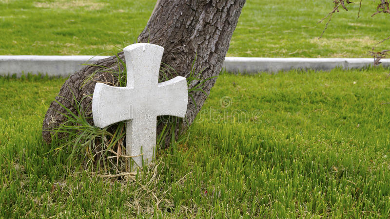 One piece stone rood in the base of a tree. A white rood in the base of a tree near a highway as a remember of one died person in a accident stock photos
