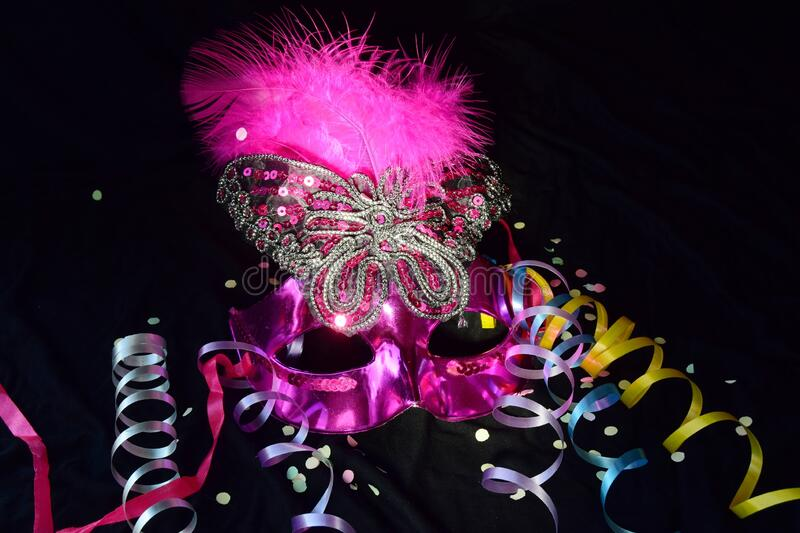 One pink carnival mask with feathers and streamers. close-up on a black background. royalty free stock image