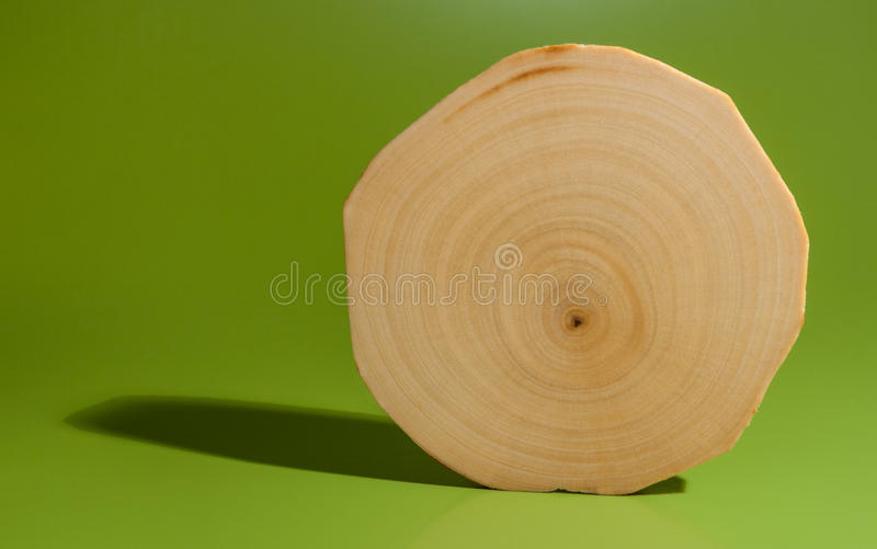 One polished and oiled alder saw cut on green background. One polished and oiled alder saw cut is standing on green background stock image