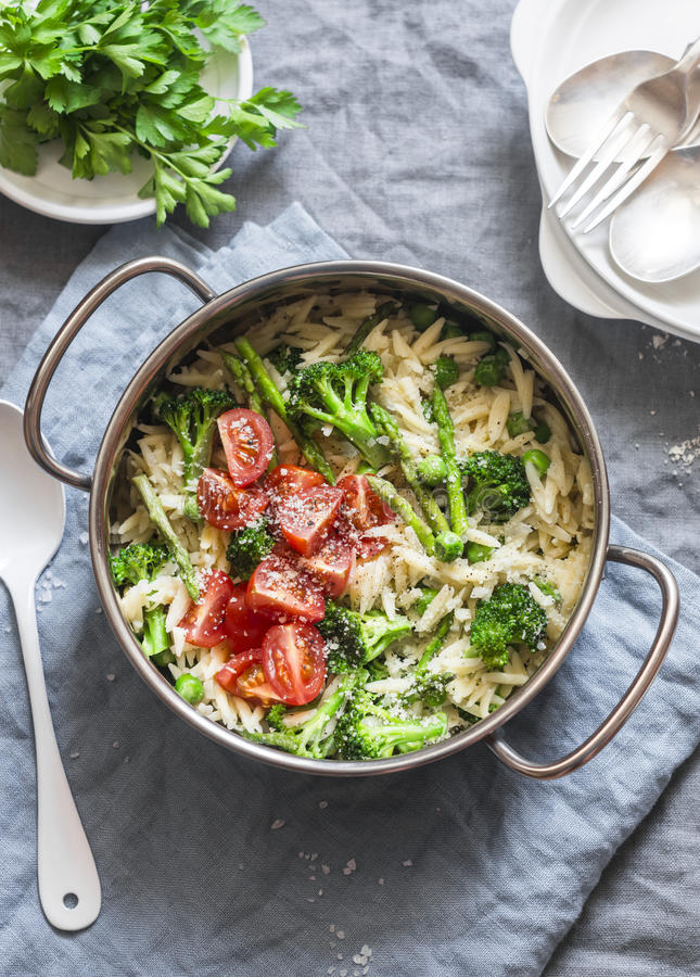 One pot orzo primavera. Orzo pasta with asparagus, broccoli, green peas and cream in a saucepan. On a light background royalty free stock photography