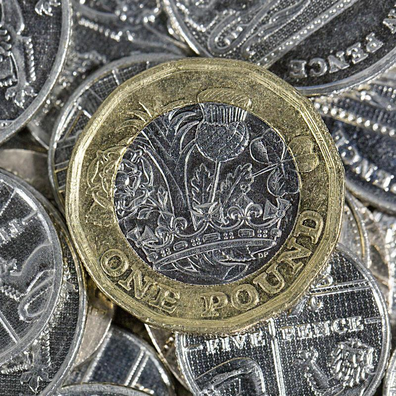 One Pound Coin - British Currency. One pound coin. The new bimetallic coins in a square format introduced as an anti-counterfeiting measure in 2017 stock photography