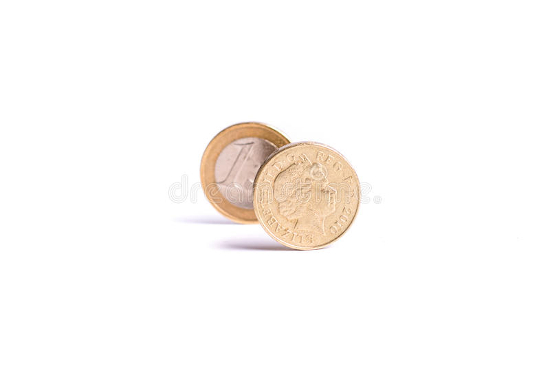 One Pound coin stand in front of the one Euro coin on white back royalty free stock photos