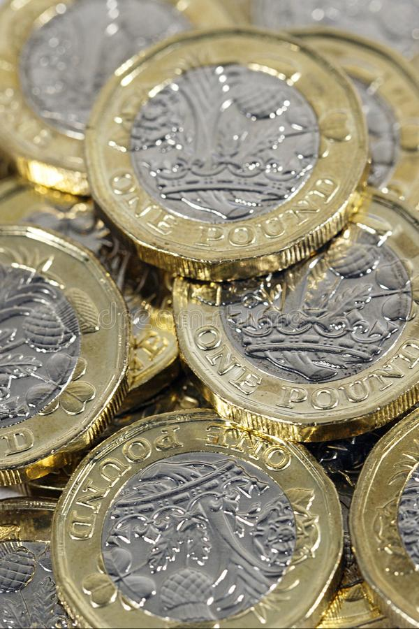 One Pound Coins - British Currency. One pound coins in a vertical format. The new bimetallic coins introduced as an anti-counterfeiting measure in 2017 stock photo