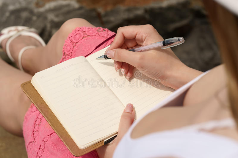 One pretty european woman is sittin on a stone c and writing some idea, letter or job by pen in her note book stock images