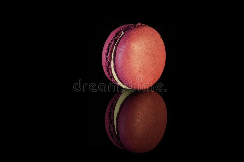 One purple berry macaron with yellow filling. Served on black mirror background with reflection stock photography