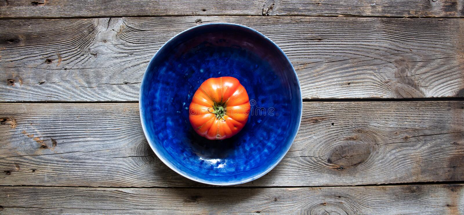 One rare heirloom beefsteak tomato isolated in beautiful blue dish royalty free stock image