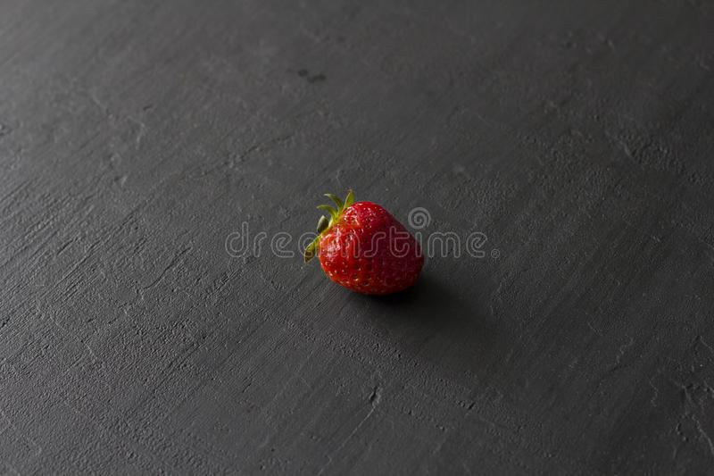 One red beautiful strawberry close-up, on a black dark concrete background. Minimalism. Side view, Copy Space For Your Text. Macro stock photography