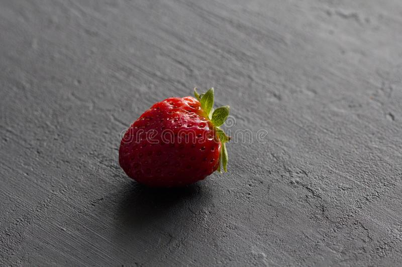 One red beautiful strawberry close-up, on a black dark concrete background. Minimalism. Side view, Copy Space For Your Text. Macro stock photos