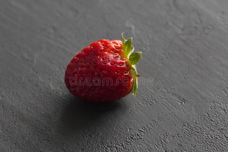 One red beautiful strawberry close-up, on a black dark concrete background. Minimalism. Side view, Copy Space For Your Text. Macro royalty free stock images