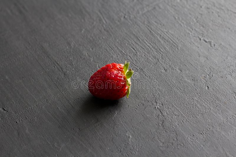 One red beautiful strawberry close-up, on a black dark concrete background. Minimalism. Side view, Copy Space For Your Text. Macro royalty free stock photography