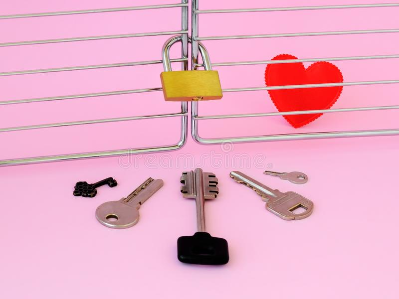 One red silk heart is in a cage locked with padlock. Five different keys in front of this cage. To pick up the key to the heart royalty free stock photography