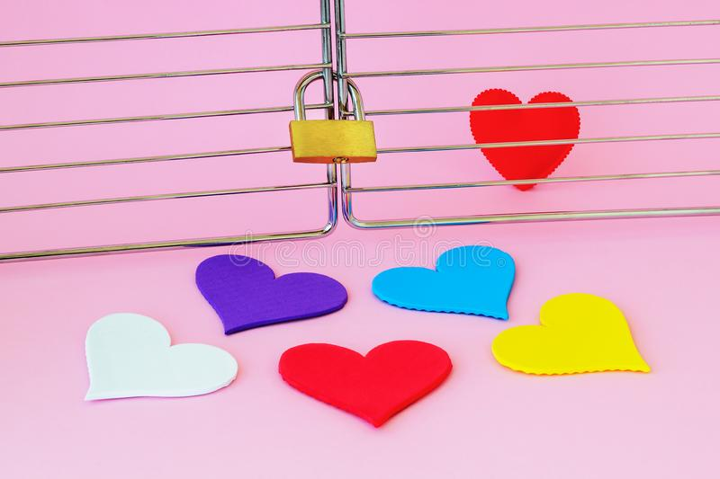 One red silk heart is in a cage locked with padlock. Five multicolored hearts are outside. To find the true love among people and royalty free stock photos